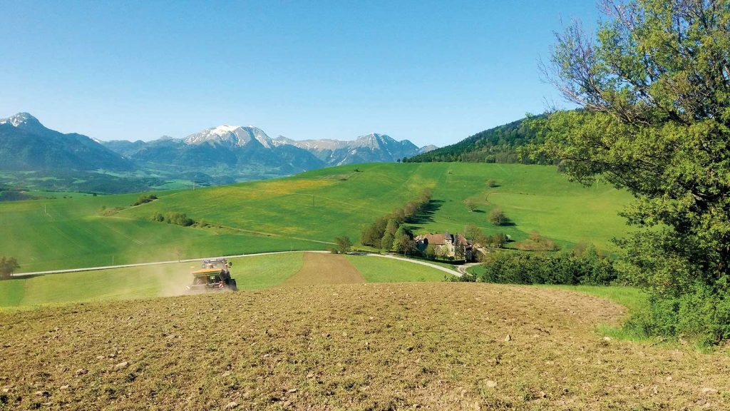 An alpine field with a tractor and snow-capped mountains in the distance.