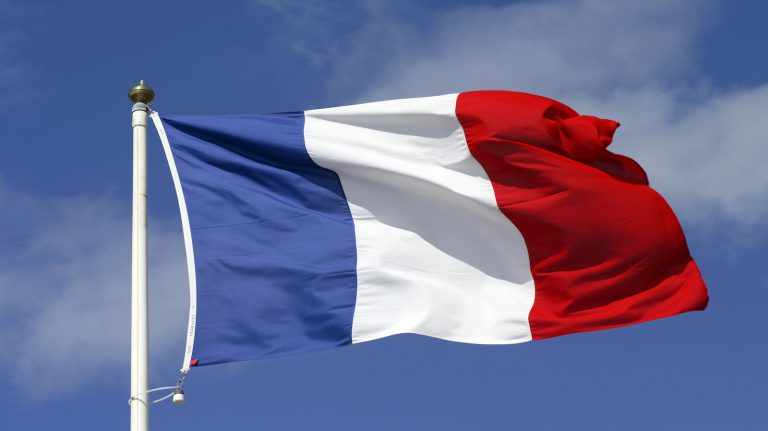 french flag waving against blue sky