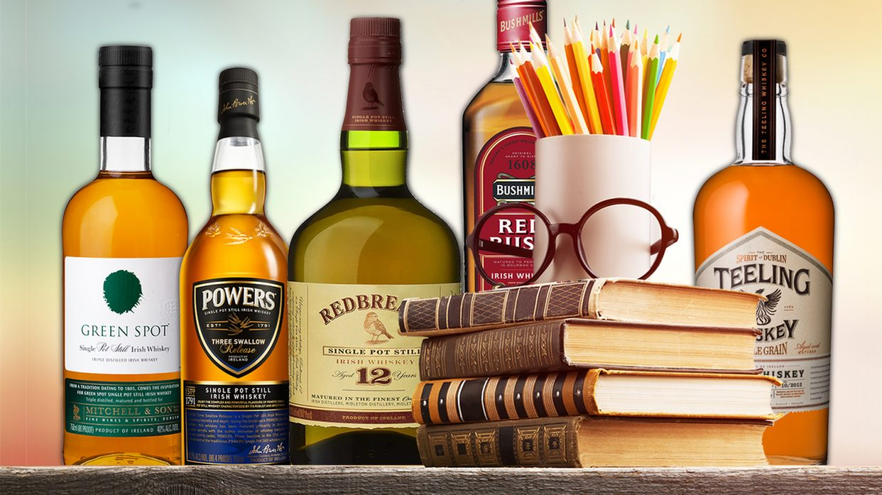 bottles of Irish whiskey arranged with a stack of books, eyeglasses, and a cup of pencils