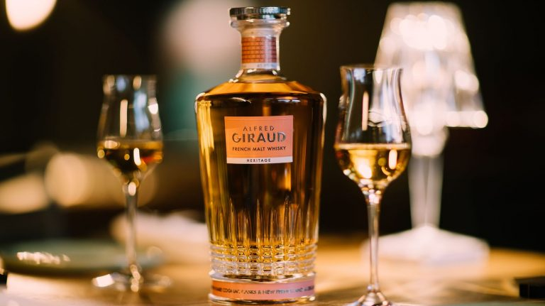 A bottle of Alfred Giraud Heritage French blended malt whisky with two stemmed tasting glasses.