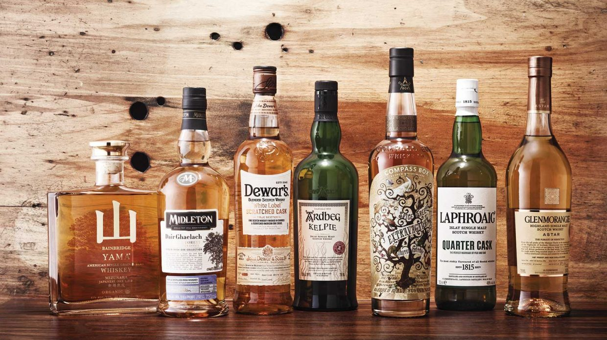 Several bottles of whiskies matured in custom-made casks rest on a wooden surface in front of a wooden wall.