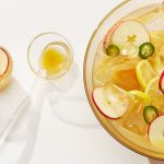 A bowl of Galway Cider whisky punch, garnished with apple, jalapeño, and lemon slices, rests on a white surface next to two punch-filled glass cups with a serving spoon.