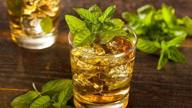 A cocktail garnished with fresh mint resembling The Howdie's Dram whisky punch rests atop a wooden surface, next to more fresh mint.