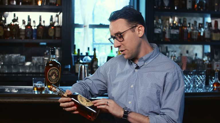 A young man wearing glasses sitting at a bar reading the label of a bottle of bourbon