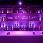 Purple light bathing a bar with The Macallan and bottles of whisky in the background