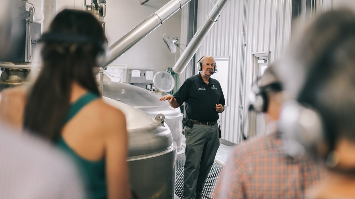 Master distiller Steve Nally stands next to distilling machinery at Bardstown Bourbon Co., while leading a tour.