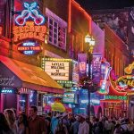 A strip of bars with neon signs advertising honky-tonky music along Lower Broadway, a major thoroughfare in downtown Nashville, Tennessee.
