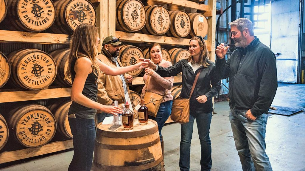 Visitors to Pennington Distilling Company in Nashville, Tennessee's Nations neighborhood stand around a whiskey barrel, upon which rests two bottles of whiskey, as they taste whiskey in the small tasting area, with whiskey barrels resting on racks in the background.