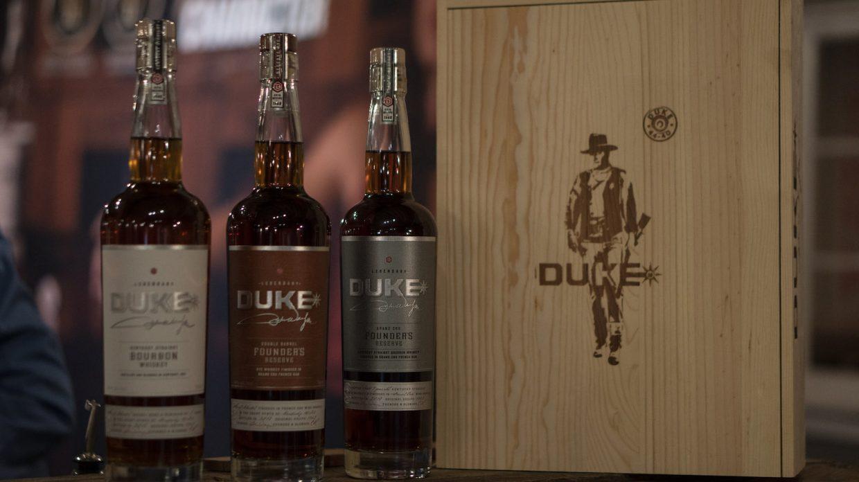 lineup of duke spirits bourbon and rye with a box showing John Wayne