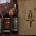 lineup of duke spirits bourbon and rye with a box showing John Wayne