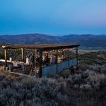 Guests of the Lodge at Blue Sky in Wanship, Utah, near High West's newer, larger distillery, assemble under a wooden structure outside at dusk, tasting what is likely whiskey.