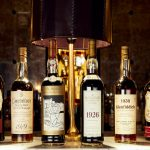 bottles of rare whisky including 1926 macallan 60 year old valerio adami and fine and rare lined up on a table