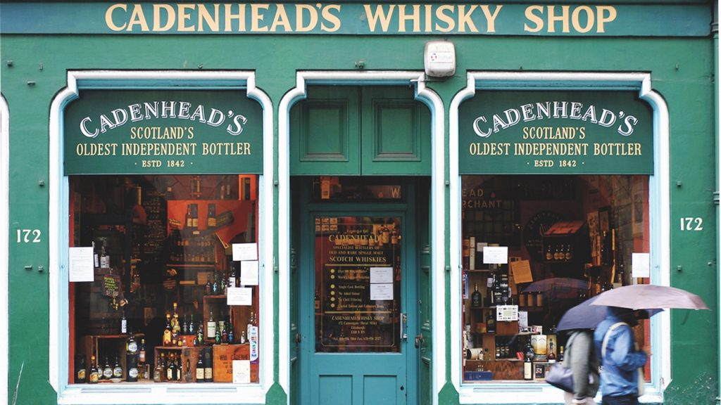 The lively green exterior of Cadenhead's Whisky Shop in Edinburgh, Scotland.