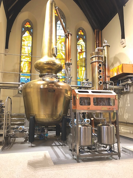 A large Kentucky-made copper still sits in front of stained-glass windows at Dublin's Pearse Lyons Distillery.