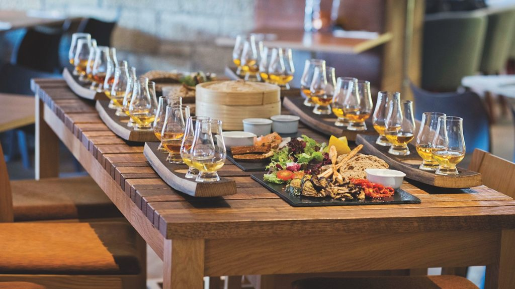 Six tasting trays are set up with three nosing glasses each, all filled with about an ounce and a half of whisky. In between the trays there are trays of food—some crackers, bread, cheese, and salad.