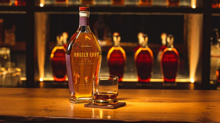 Bottle of Angel's Envy Tawny Port Cask-Finished Bourbon on a bartop with a glass of the whiskey and more Angel's Envy bottles in the background