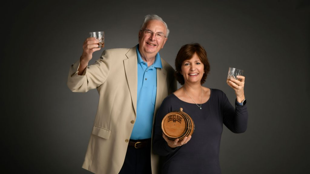 Retired attorney and native Kentuckian William Elam, who designed the Forever Aging urn—a small cask made from the wood of bourbon barrels, designed specifically to hold the ashes of the dead—and Andrea Bogard LeBlanc, founder of Bogati Urn Company in Sarasota, Florida, stand next to each other, raising glasses filled with what appears to be whisky; Bogard LeBlanc also holds one of the Forever Aging urns her company sells to funeral homes and crematories.
