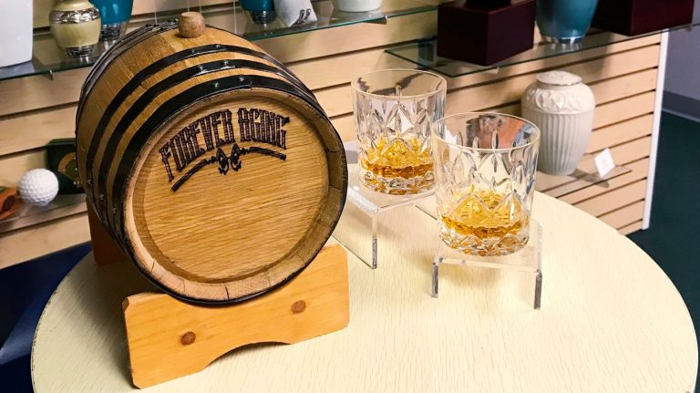 The trademarked Forever Aging urn—a small cask, made from the wood of bourbon barrels, to hold the ashes of the dead—rests on a table alongside two rocks glasses containing what appears to be whisky in the Bogati Urn Company showroom in Sarasota, Florida.
