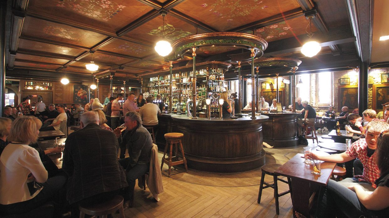 A view of the interior of Òran Mór, an upscale whisky bar at the center of an arts and entertainment venue located in a former church, where patrons sit among wooden fixtures and furnishings, at tables and at the bar, imbibing beer and spirits, under lights hanging from the ceiling, in Glasgow.