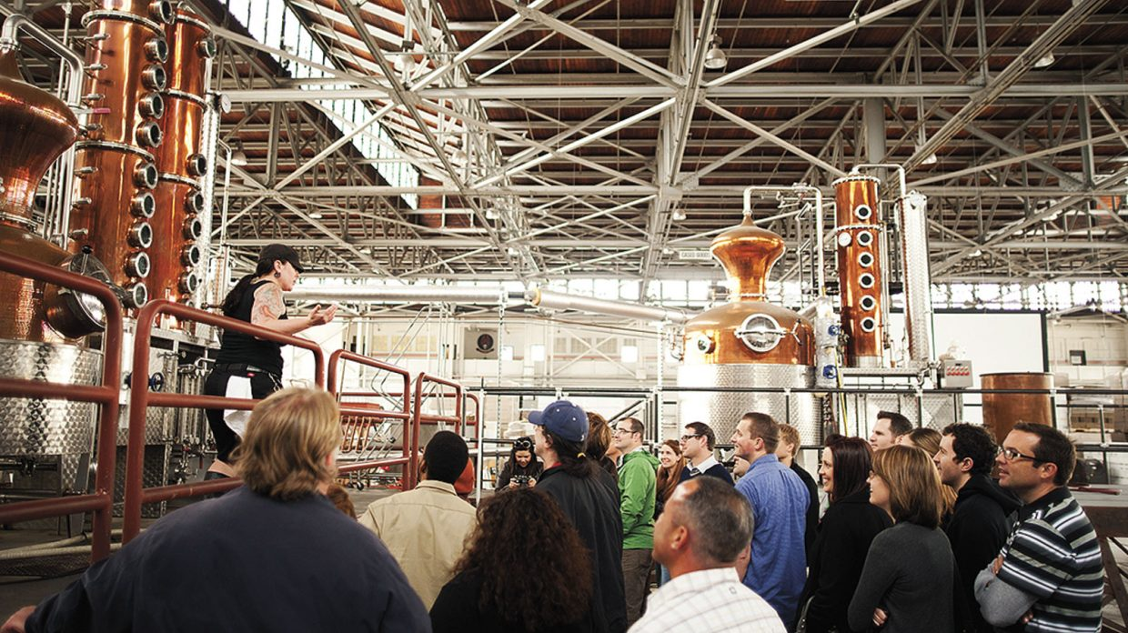 A woman with dark hair in a ponytail, wearing a black tank top that reveals her tattooed arms, stands in front of a still addressing what appears to be a crowd of distillery visitors, some of them smiling, at St. George Spirits, located in a former airplane hangar in Alameda, about 15 miles from San Francisco.