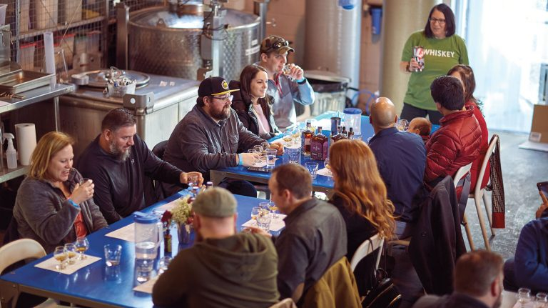 Members of whisky club Pittsburgh Whiskey Friends sit around a table at Wigle Whiskey in Pittsburgh, Pennsylvania on Dec. 21, 2019, tasting whiskeys, with distilling equipment visible in the background.