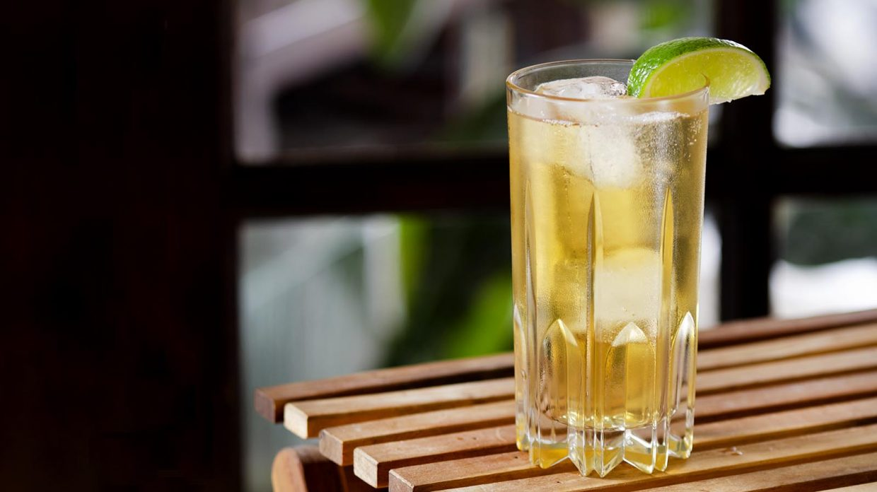 Collins glass filled with whiskey and ginger ale, with a lime wedge, on a wooden slat table