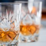 Close up color image depicting two fine crystal glasses of malt whisky on a white wooden surface. The glasses of whisky are surrounded by whisky paraphernalia such as a glass decanter and a hip flask. Room for copy space.