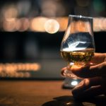 Close up shot of a hand holding a Glencairn single malt whisky glass.