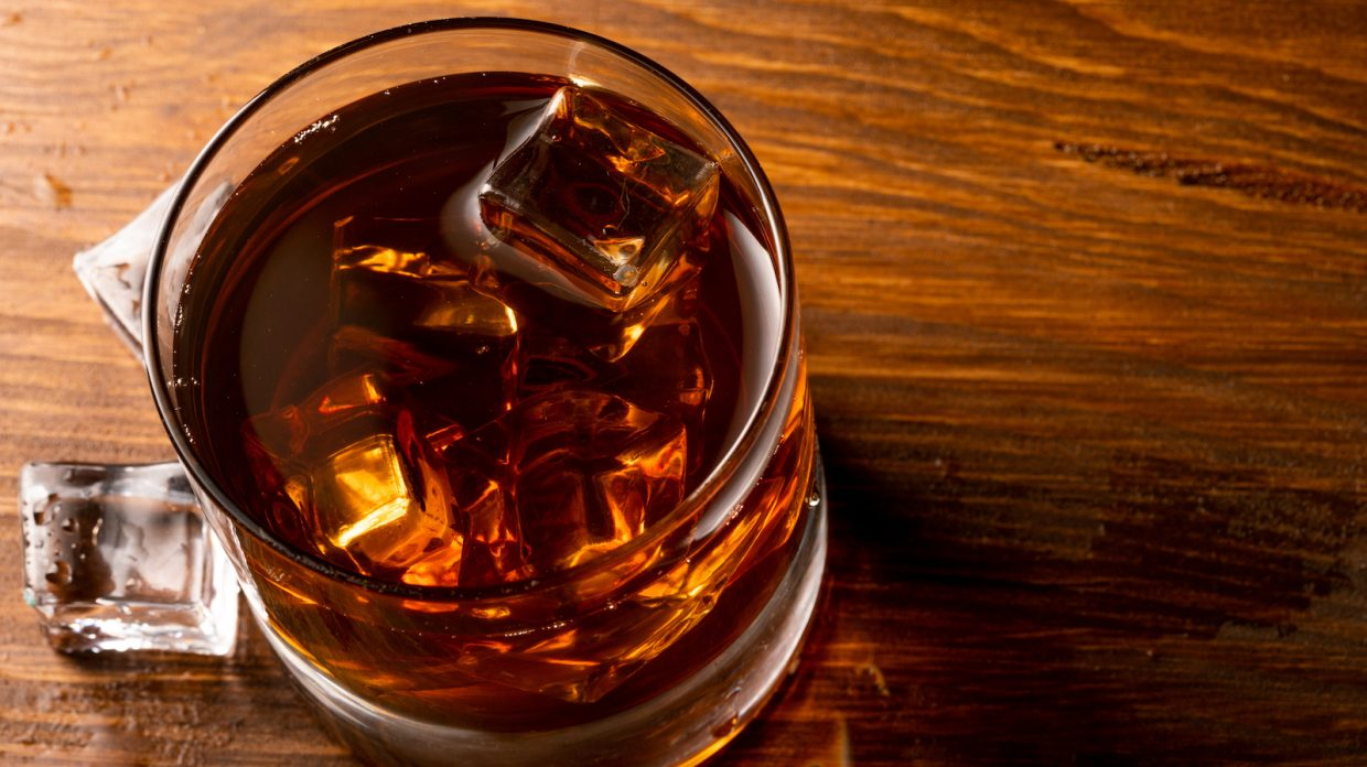whiskey glass and whiskey with ice cubes