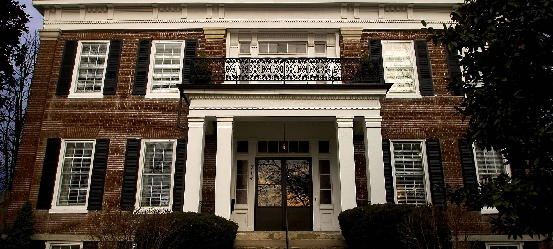 Bourbon Manor B&B has a brick facade with black shutters, white portico entrance with metal railing balcony
