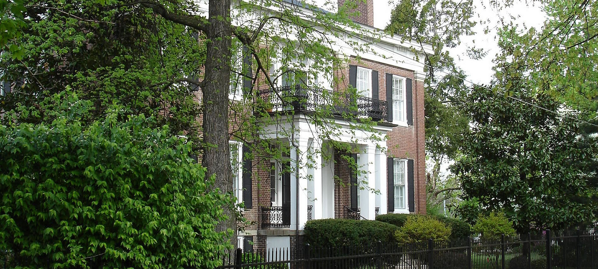 Bourbon Manor B&B has a brick facade with black shutters, white portico entrance with metal railing balcony and mature trees