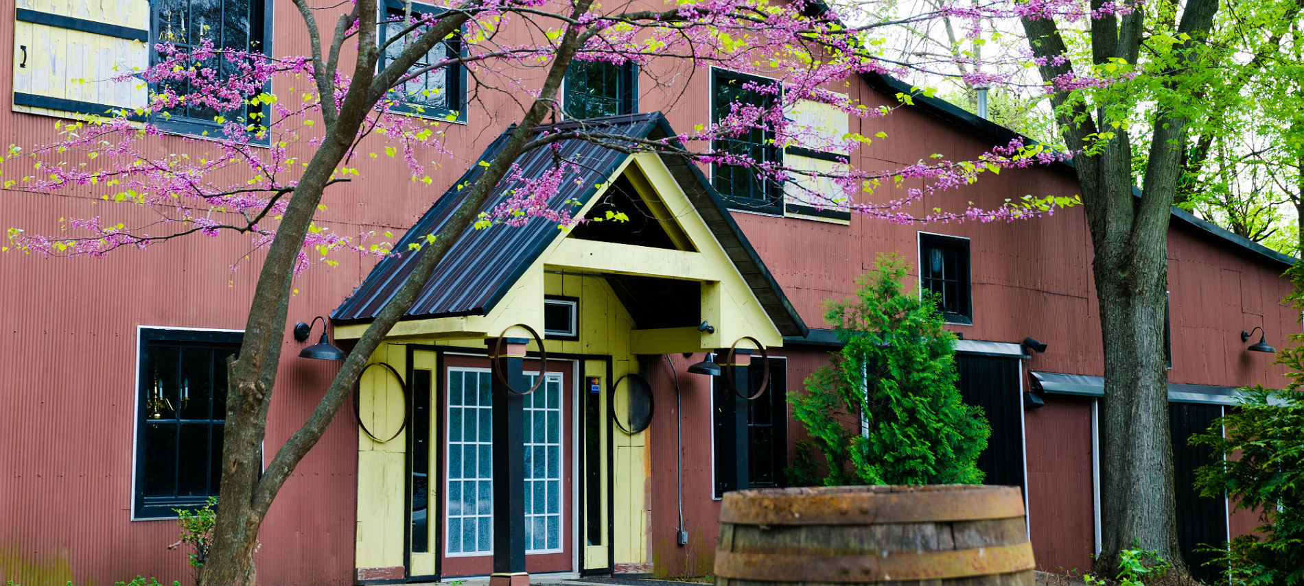 Bourbon Manor B&B's Bourbon Bar Lounge with red facade, dark trim and white entry and shutters and blooming foreground trees