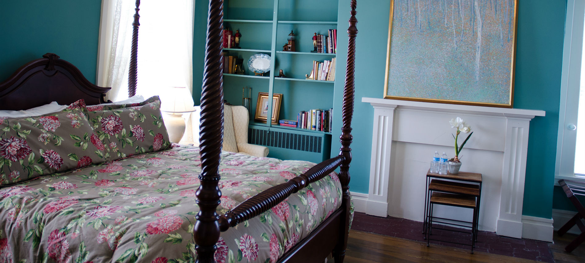 Guestroom with teal walls, white trim and curtains, built-in bookcase and bed with green and pink floral bedding