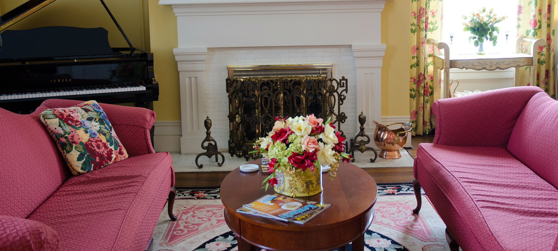Parlor with yellow walls, white fireplace, two scarlet love seats facing each other, wooden coffee table and baby grand piano
