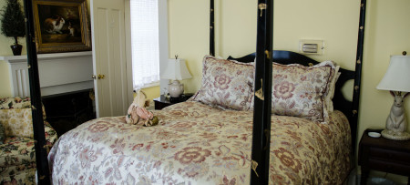 Guestroom with pale yellow walls, dark four-poster bed with cream and pink floral comforter and pillows