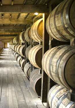 The interior of a typical bourbon storehouse with wooden walls, windows, plank flooring and row after row of wooden bourbon barrels