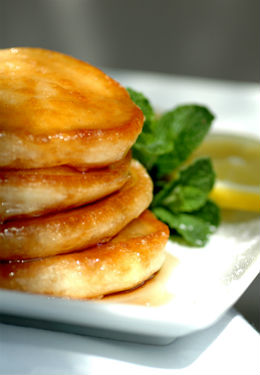 Stack of four fluffy lemon souffle pancakes on a white square plate with mint sprig and lemon slice