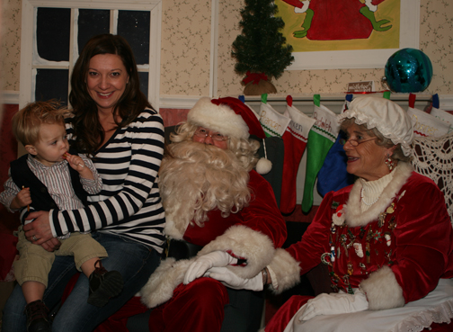 Santa and Mrs. Clause posing with mother and child at the Mistletoe Market