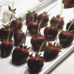Several strawberries with stems which have been dipped in chocolate