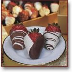 3 strawberries dipped in milk and white chocolate, decorated with a chocolate drizzle