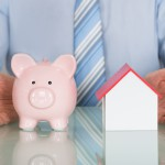 Businessman Protecting Piggy Bank And House Model