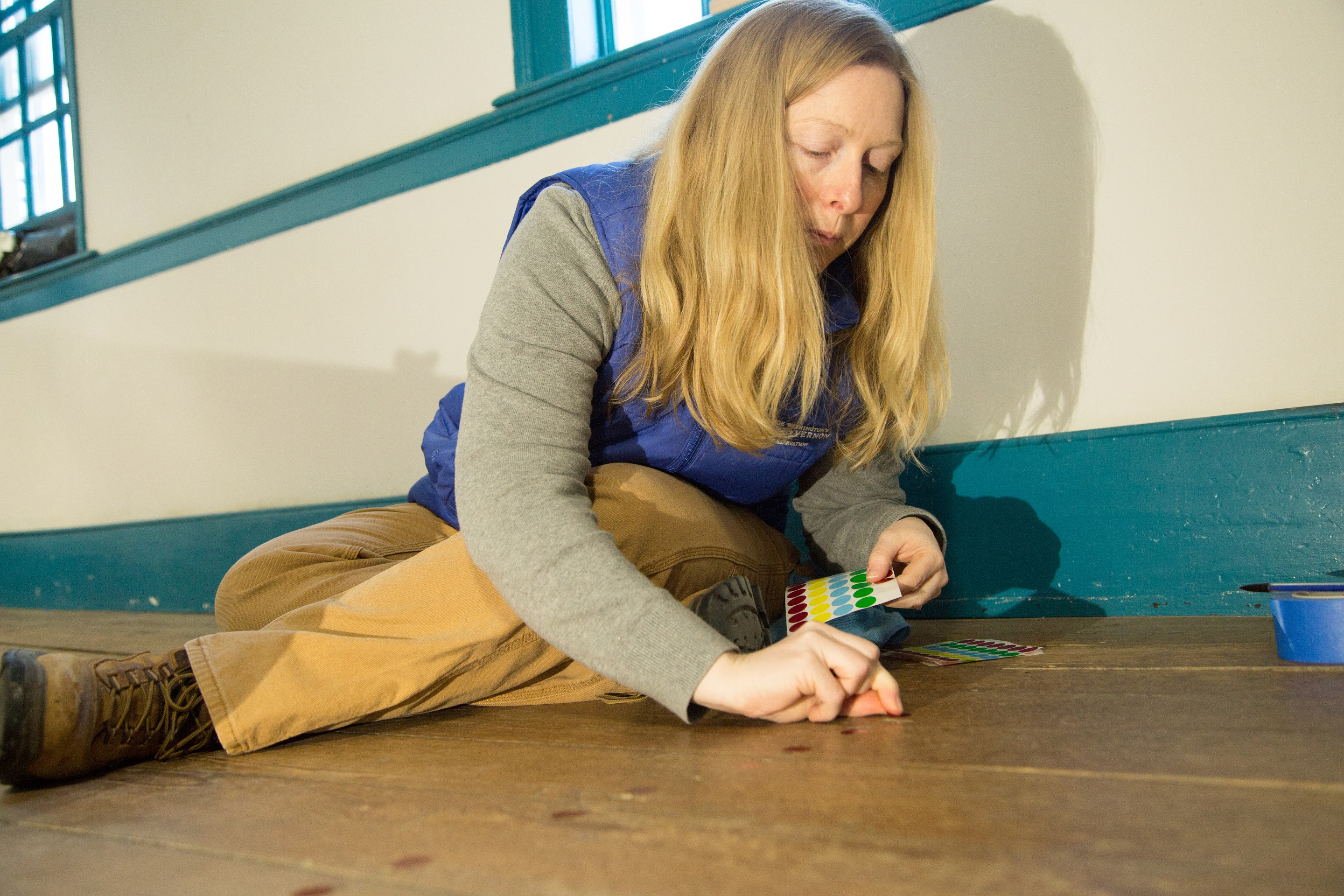 Architectural Historian, Caroline Spurry, applies color coded stickers to the floor to identify the floor nail types.