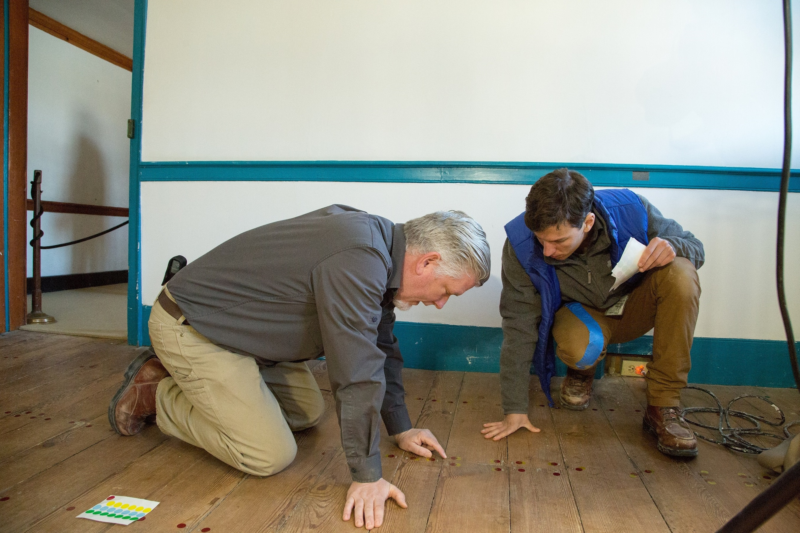 Director of Architecture, Thomas Reinhart, and Preservation Specialist, Eric Litchford, study the Blue Room floor nail patterns.