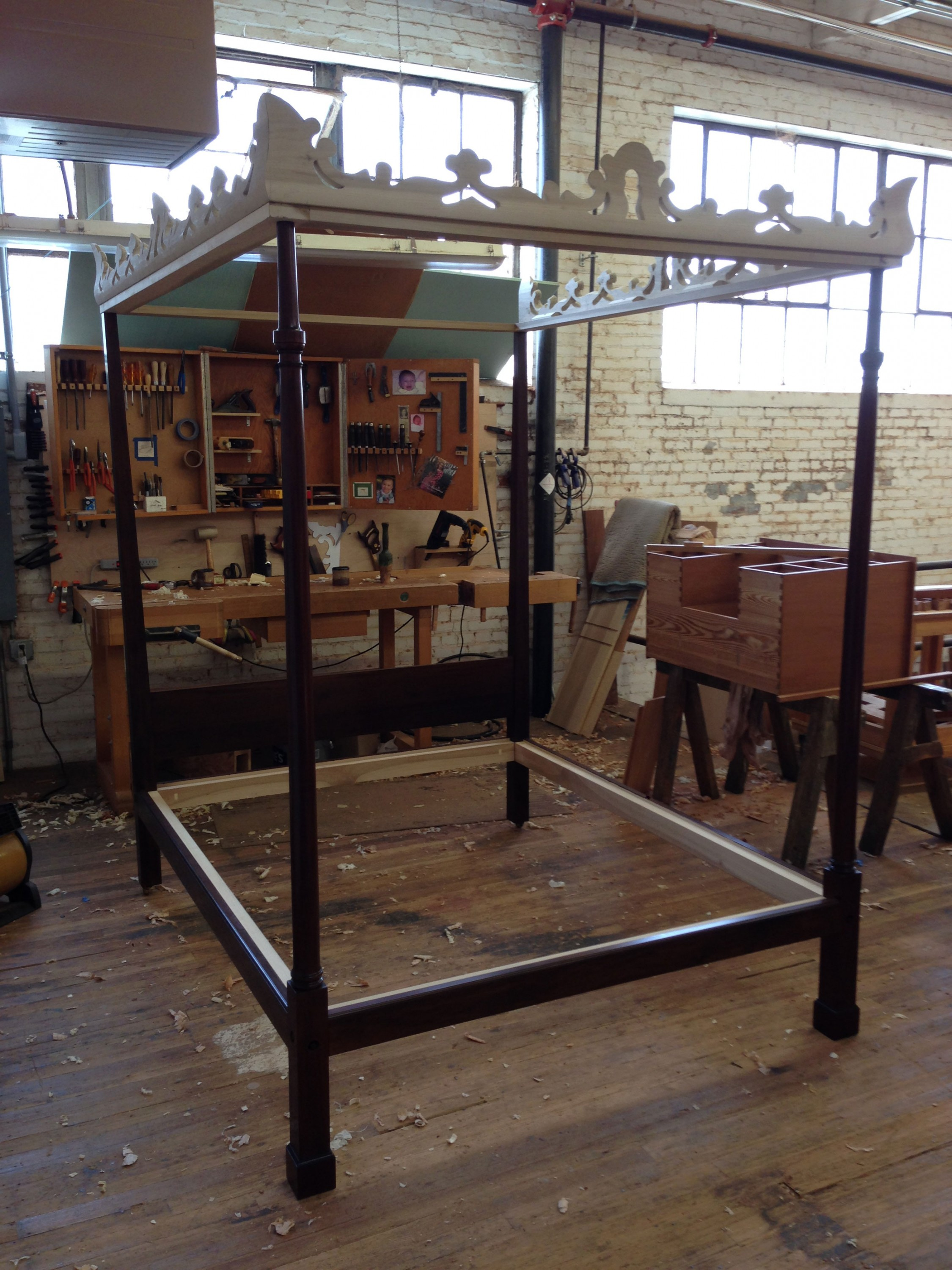 The reproduction dressing table, in progress, sits on the workbench to the side of the completed reproduction bedstead. Courtesy of Harrison Higgins, Inc., Richmond, Virginia.