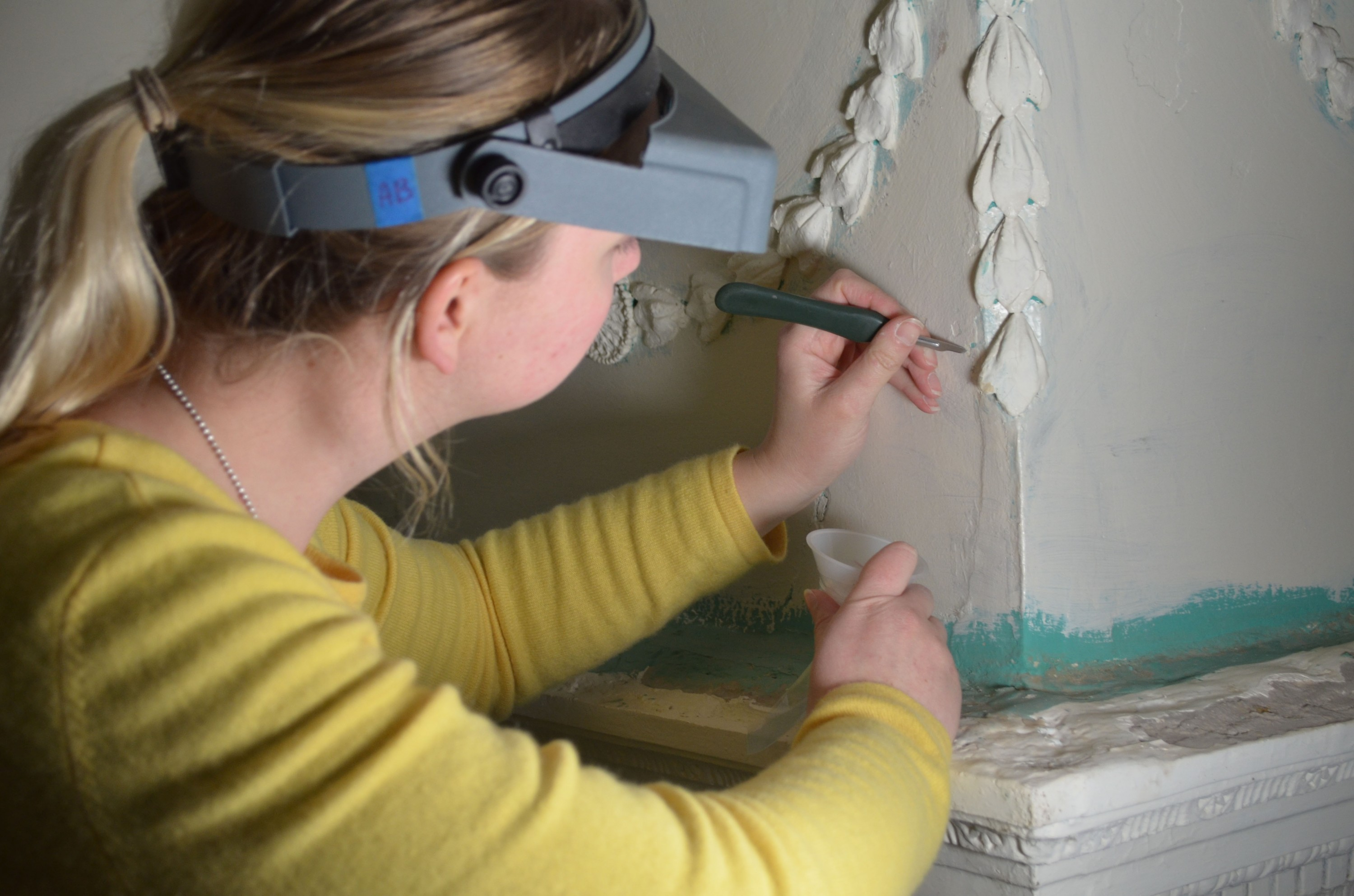 Conservator Amelia Jensen takes paint samples for analysis.
