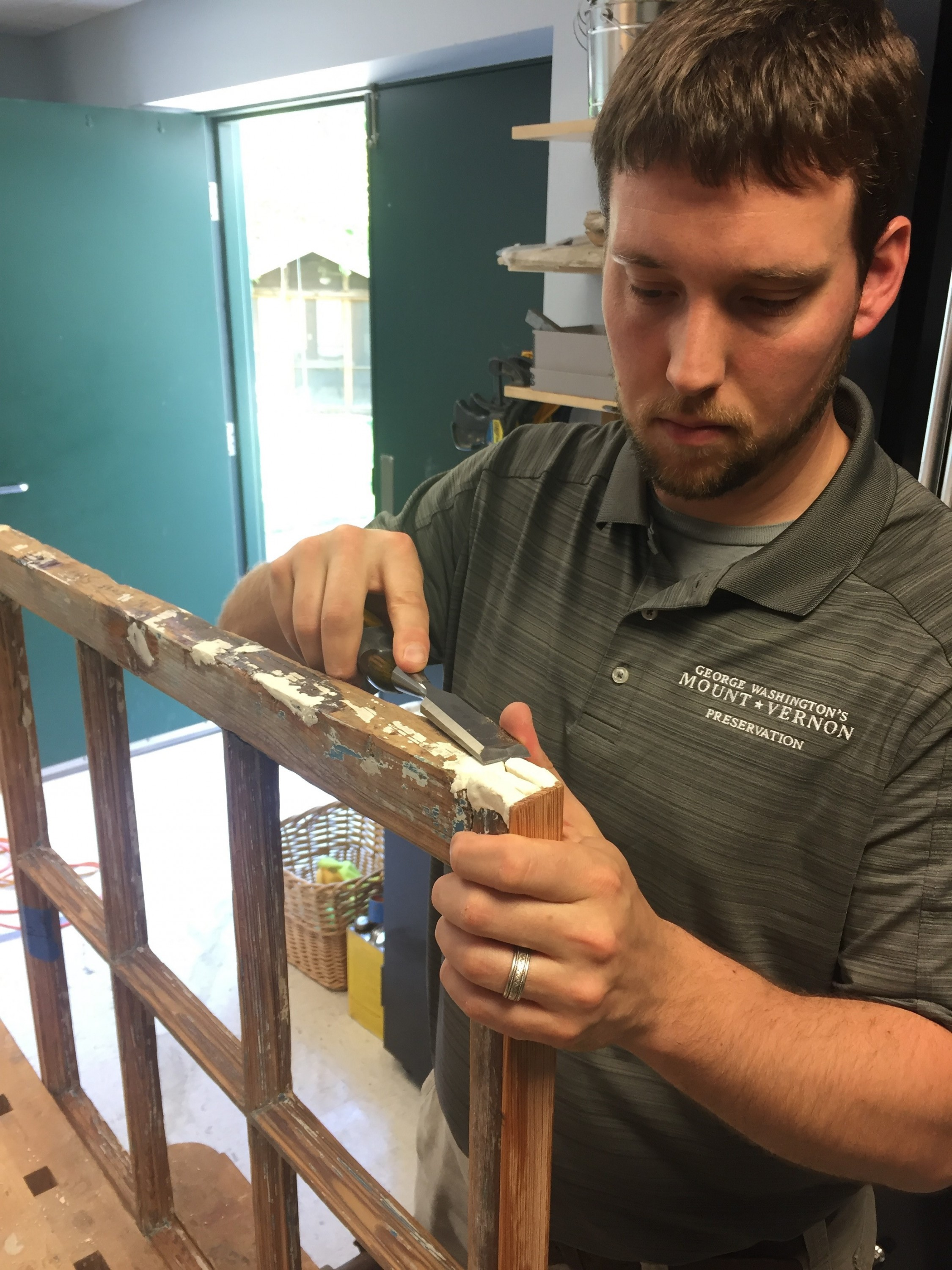 Architectural Conservator, Steve Stuckey, shaping an epoxy repair to match the dimensions of the sash frame with a chisel.