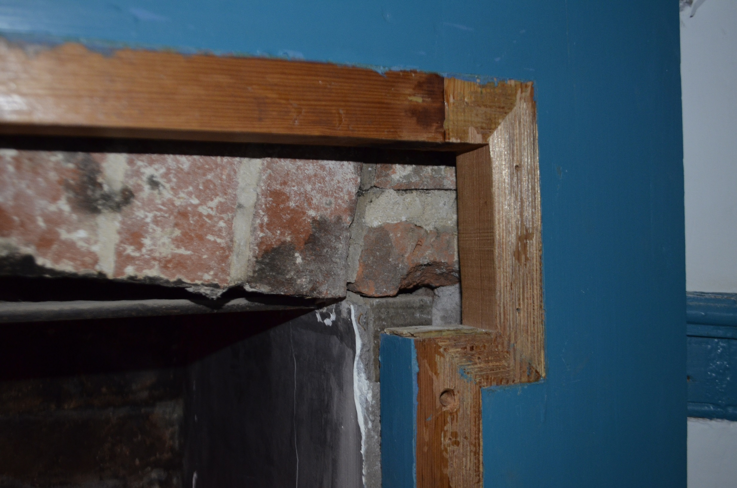 Corner of mantel with decorative lintel and applied trim removed.