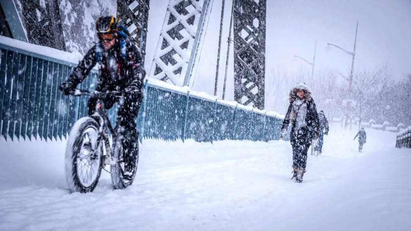 A cyclist riding a fat bike, alongside pedestrians on the Alexandra Bridge in winter.
