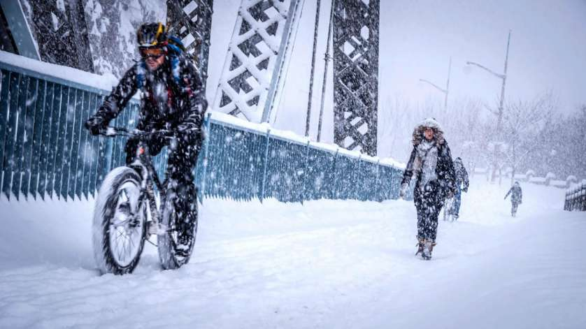 A cyclist riding a fat bike, alongside pedestrians on the Alexandra Bridge in winter.