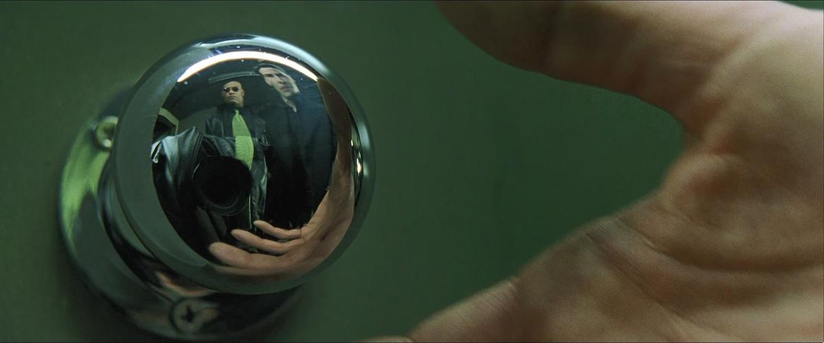 imagem que mostra cena do filme matrix, reflexo da câmera mostrada na maçaneta da porta
